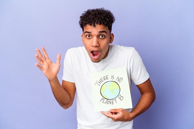 Młody afroamerykanin kędzierzawy mężczyzna na białym tle trzyma a nie ma plakatu planety b zaskoczony i zszokowany.