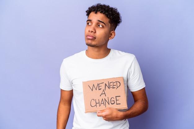 Młody afroamerykanin, kędzierzawy mężczyzna na białym tle trzyma potrzebujemy zmiany karton zdezorientowany, czuje się niepewny i niepewny.
