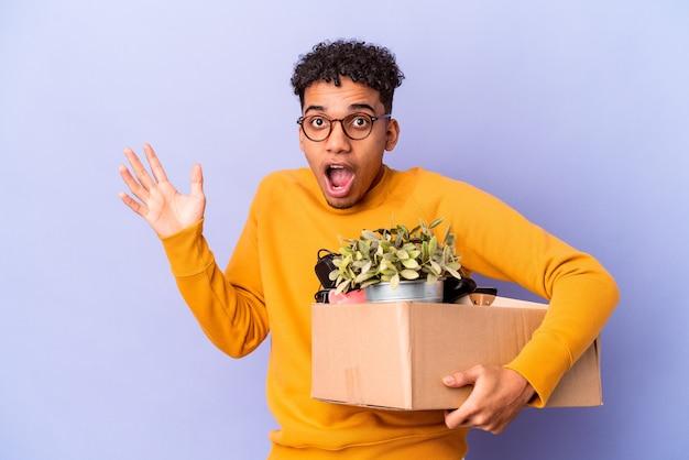 Młody afroamerykanin kręcone człowiek przenosi się do nowego domu zaskoczony i zszokowany.