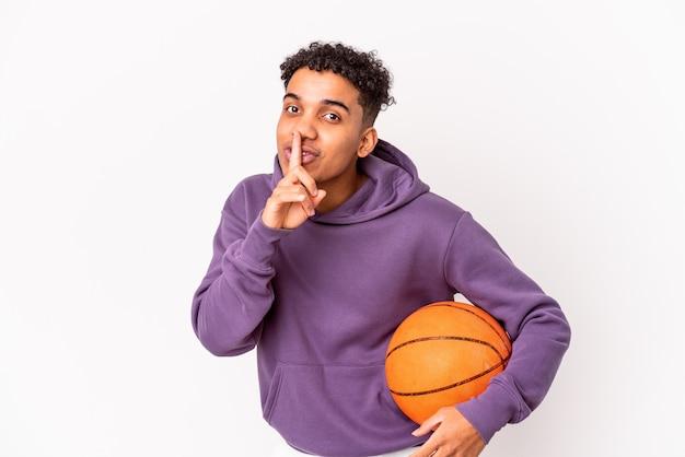 Młody afroamerykanin kręcone mężczyzna gra w koszykówkę, zachowując tajemnicę lub prosząc o ciszę.