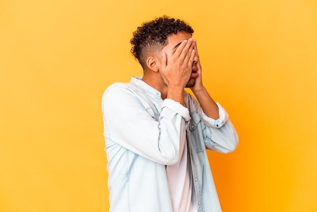 Młody afroamerykanin kręcone mężczyzna na białym tle na fioletowy boi się zakrywających oczy rękami.