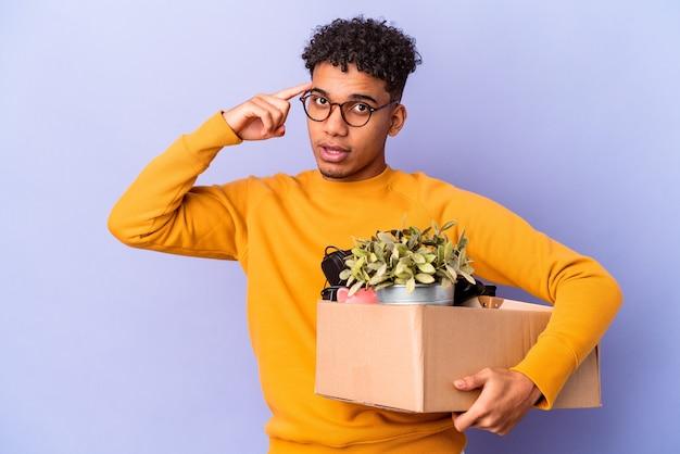 Młody afroamerykanin kręcone mężczyzna na białym tle przenosi się do nowego domu wskazując świątynię palcem, myśląc, koncentruje się na zadaniu.