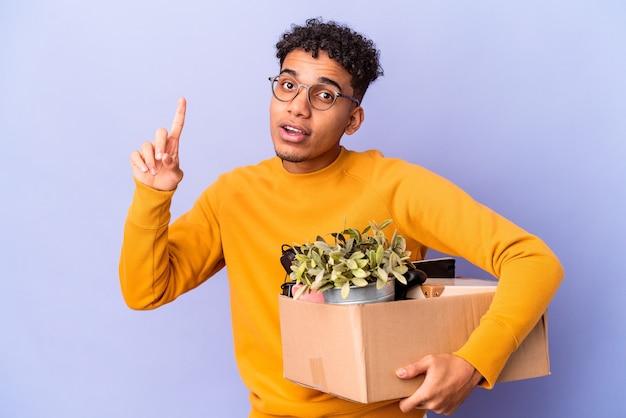 Młody afroamerykanin kręcone mężczyzna na białym tle przeprowadzka do nowego domu mając świetny pomysł, pojęcie kreatywności.