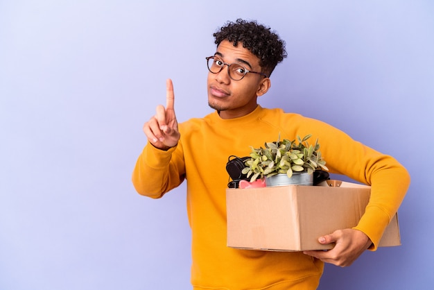 Młody afroamerykanin kręcone mężczyzna na białym tle przeprowadzka do nowego domu pokazując numer jeden palcem.