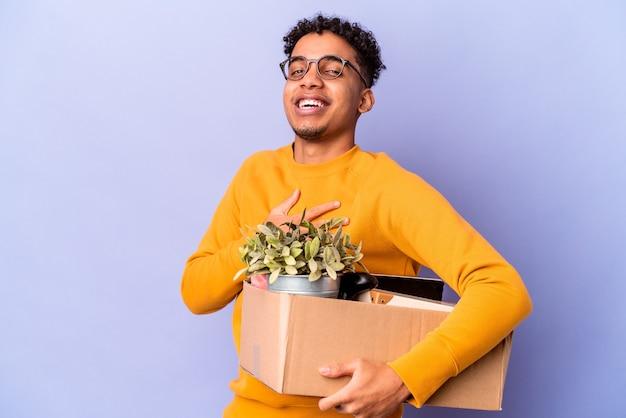 Młody afroamerykanin kręcone mężczyzna na białym tle przeprowadzka do nowego domu śmieje się głośno, trzymając rękę na piersi.