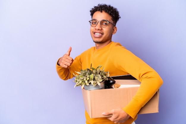 Młody afroamerykanin kręcone mężczyzna na białym tle przeprowadzka do nowego domu uśmiechnięty i podnoszący kciuk do góry