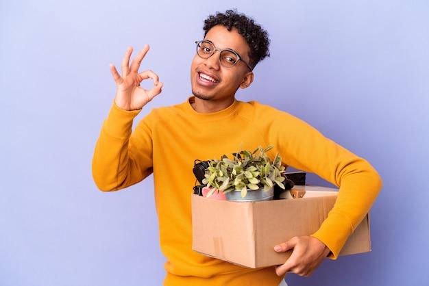 Młody afroamerykanin kręcone mężczyzna na białym tle przeprowadzka do nowego domu wesoły i pewny siebie, pokazując ok gest.