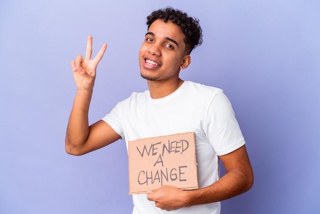 Młody afroamerykanin kręcone mężczyzna na białym tle trzymając musimy karton zmiany pokazujący numer dwa palcami.