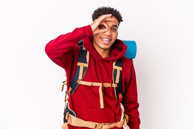 Młody afroamerykanin kręcone podróżnik mężczyzna na białym tle podekscytowany utrzymując ok gest na oko.