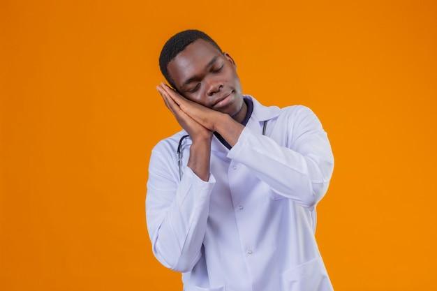 Młody afroamerykanin lekarz ubrany w biały fartuch ze stetoskopem trzymając dłonie razem, opierając głowę na dłoniach, wyglądający na zmęczonego, chce spać