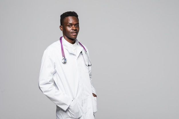 Młody afroamerykanin lekarz w białym mundurze na białym tle stojący z rękami w kieszeniach wyglądający profesjonalnie i bardzo kompetentnie w dziedzinie specjalizacji medycznej