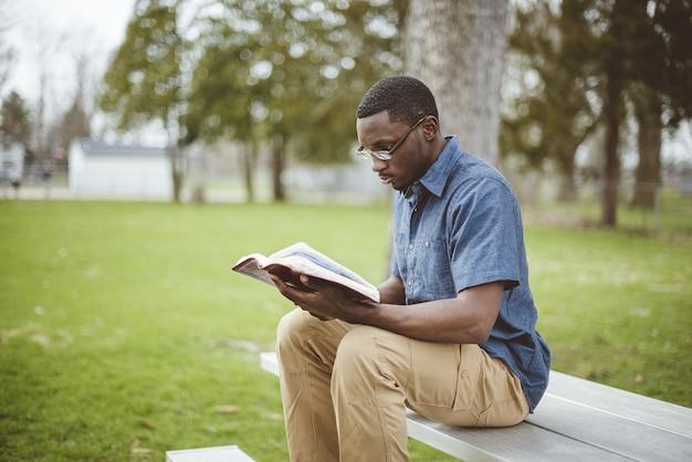 Młody afroamerykanin mężczyzna siedzi na ławce i czyta biblię