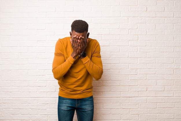 Młody afroamerykanin murzyn czuje się smutny, sfrustrowany, zdenerwowany i przygnębiony, zasłaniając twarz obiema rękami, płacząc przy ścianie z cegły
