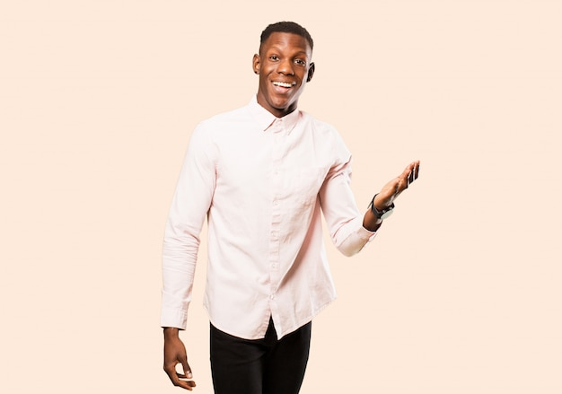 Młody afroamerykanin murzyn czuje się szczęśliwy, zaskoczony i wesoły, uśmiecha się pozytywnie, realizuje rozwiązanie lub pomysł na beżowej ścianie
