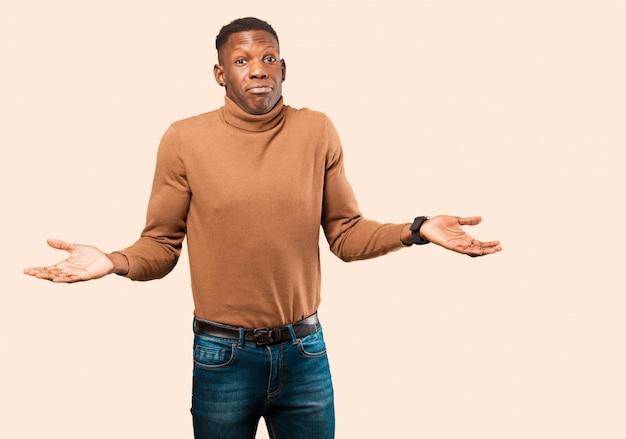 Młody afroamerykanin murzyn czuje się zdziwiony i zdezorientowany, wątpi, waży lub wybiera różne opcje z zabawnym wyrazem twarzy na beżowej ścianie