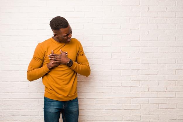 Młody afroamerykanin murzyn wygląda smutno, zraniony i ze złamanym sercem, trzymając obie ręce blisko serca, płacze i czuje się przygnębiony na tle ceglanego muru
