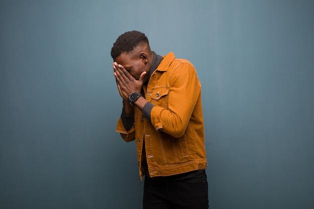 Młody afroamerykanin murzyn zakrywający oczy rękami o smutnym, sfrustrowanym wyrazie rozpaczy, płaczu, widoku z boku na ścianie grunge