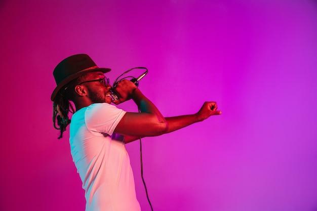 Młody afroamerykanin muzyk jazzowy śpiewa piosenkę gradientu różu
