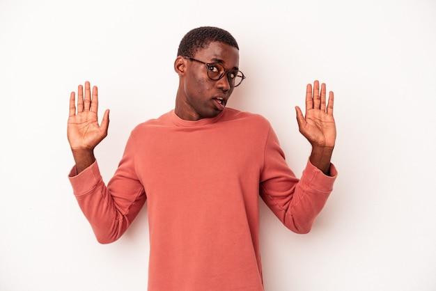 Młody afroamerykanin na białym tle jest zszokowany z powodu zbliżającego się niebezpieczeństwa