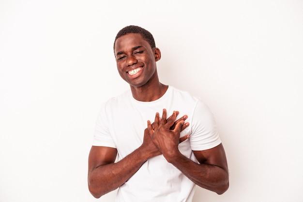 Młody afroamerykanin na białym tle ma przyjazną ekspresję, naciskając dłoń na klatkę piersiową. koncepcja miłości.