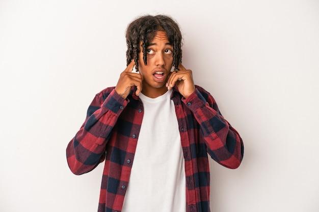 Młody afroamerykanin na białym tle na białym tle zakrywający uszy palcami, zestresowany i zdesperowany przez głośno otoczenia.
