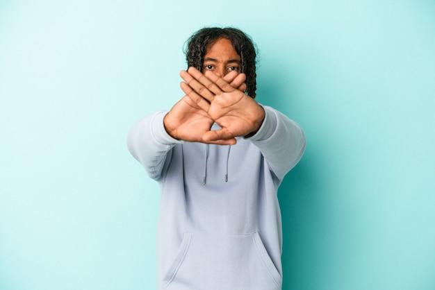 Młody afroamerykanin na białym tle na niebieskim tle robi gest odmowy
