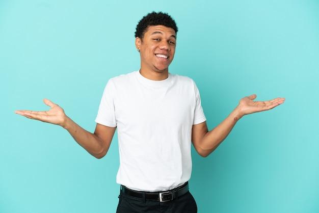 Młody afroamerykanin na białym tle na niebieskim tle ze zszokowanym wyrazem twarzy