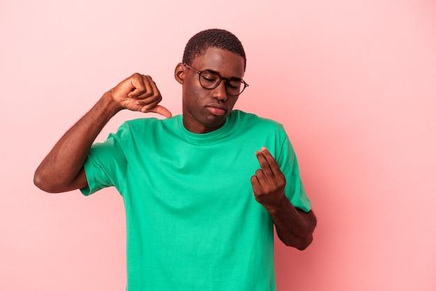 Młody afroamerykanin na białym tle na różowym tle pokazując, że nie ma pieniędzy.