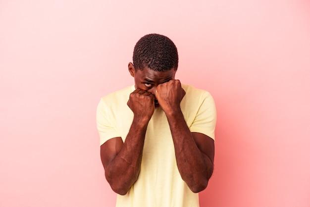 Młody afroamerykanin na białym tle na różowym tle rzucający cios, gniew, walczący z powodu kłótni, boks.