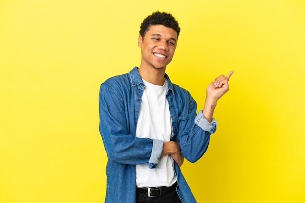 Młody afroamerykanin na białym tle na żółtym tle szczęśliwy i wskazujący w górę