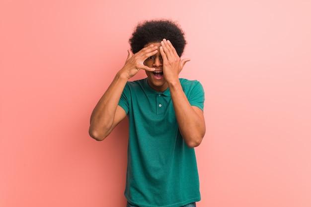 Młody afroamerykanin na różowej ścianie czuje się zmartwiony i przestraszony
