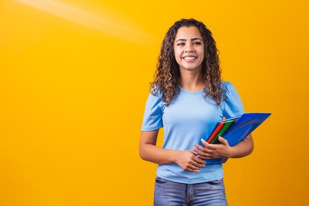 Młody afroamerykanin nastoletnia studentka w dorywczo ubrania gospodarstwa książek na białym tle na żółtym tle portret studyjny. edukacja w liceum koncepcji kolegium uniwersyteckiego. makieta miejsca na kopię