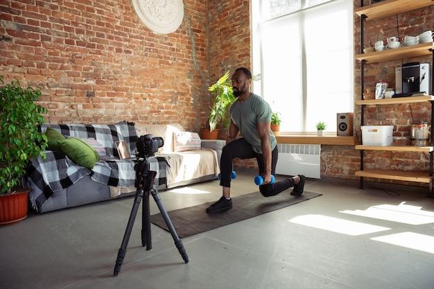 Młody afroamerykanin nauczający w domu online kursy fitness, aerobik, sportowy styl życia podczas kwarantanny, nagrywanie przed kamerą, streaming