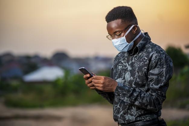 Młody afroamerykanin noszący maskę ochronną, używający swojego telefonu na zewnątrz