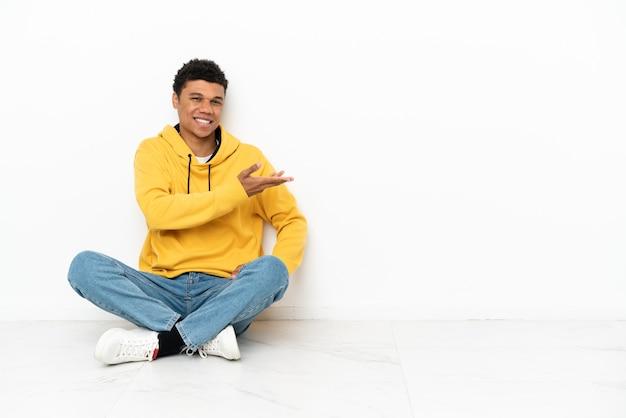 Młody afroamerykanin siedzący na podłodze na białym tle, prezentujący pomysł, patrząc w kierunku uśmiechu
