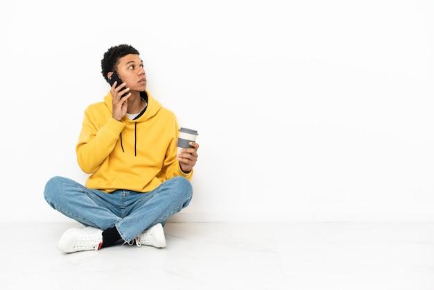 Młody afroamerykanin siedzący na podłodze na białym tle trzymający kawę na wynos i telefon komórkowy