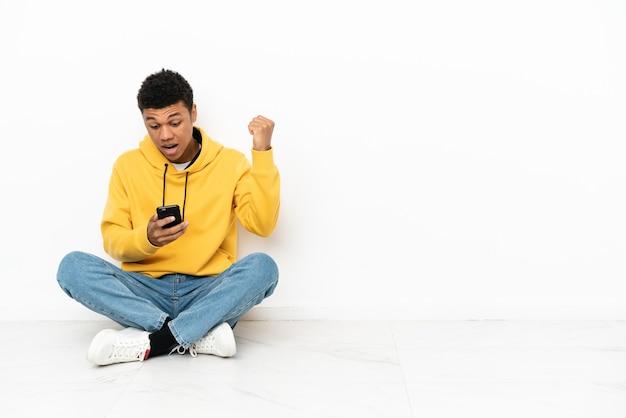 Młody afroamerykanin siedzący na podłodze na białym tle zaskoczony i wysyłający wiadomość
