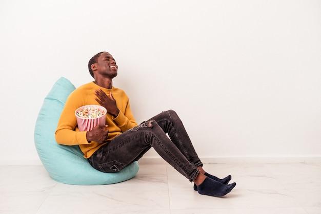 Młody afroamerykanin siedzący na ptysie jedzący popcorn na białym tle śmieje się głośno trzymając rękę na klatce piersiowej.