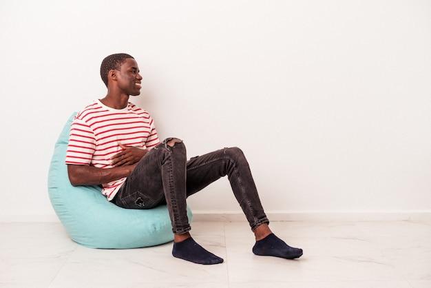 Młody afroamerykanin siedzący na ptysie na białym tle wygląda z boku uśmiechnięty, wesoły i przyjemny.