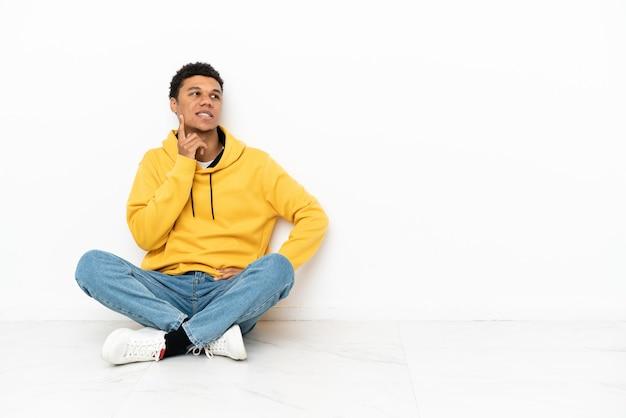 Młody afroamerykanin siedzi na podłodze na białym tle, myśląc o pomyśle, patrząc w górę