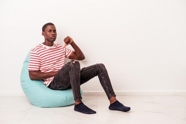Młody afroamerykanin siedzi na ptysie na białym tle, pokazując gest niechęci, kciuk w dół. koncepcja niezgody.