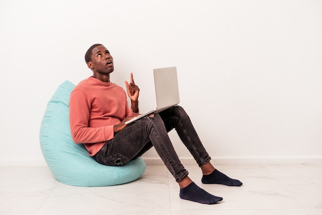 Młody afroamerykanin siedzi na zaciągnięcie za pomocą laptopa na białym tle, wskazując do góry z otwartymi ustami.