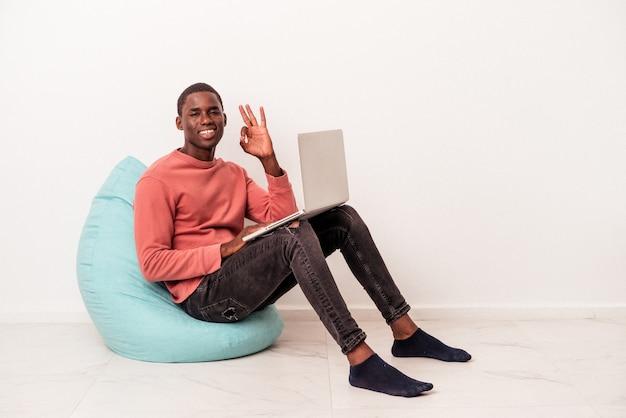 Młody afroamerykanin siedzi na zaciągnięciu za pomocą laptopa na białym tle wesoły i pewny siebie, pokazując ok gest.