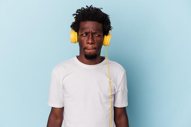 Młody afroamerykanin słuchając muzyki na białym tle na niebieskim tle zdezorientowany, czuje się wątpliwy i niepewny.