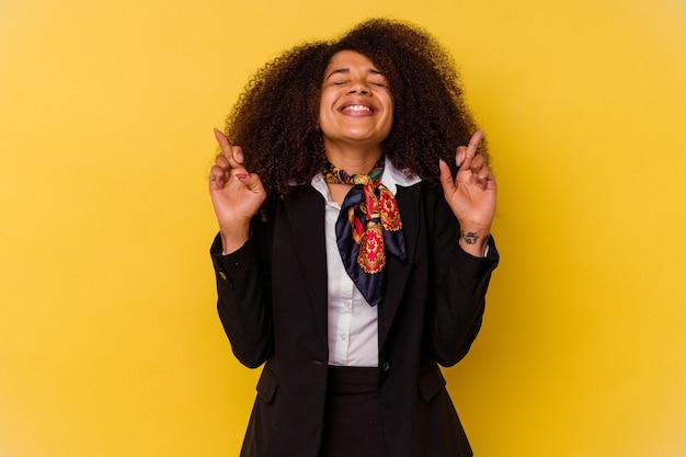 Młody afroamerykanin stewardesa na białym tle na żółtym tle skrzyżowanie palców za szczęście