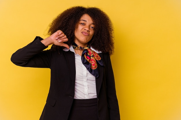 Młody afroamerykanin stewardesa na żółtej ścianie pokazujący gest niechęci, kciuk w dół. pojęcie sporu.