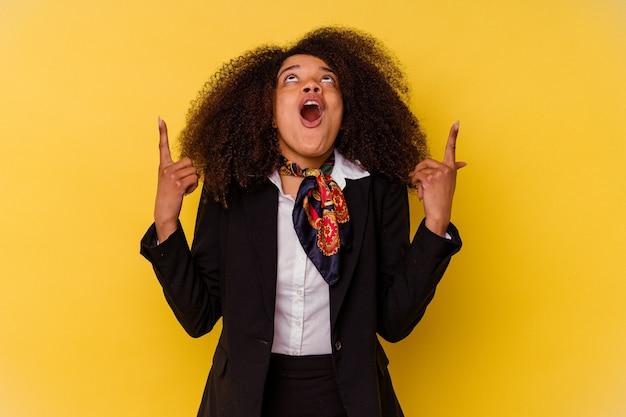 Młody afroamerykanin stewardesa na żółtej ścianie skierowany ku górze z otwartymi ustami.