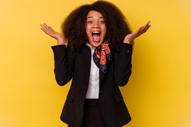 Młody afroamerykanin stewardesa na żółtej ścianie świętuje zwycięstwo lub sukces, jest zaskoczony i zszokowany.