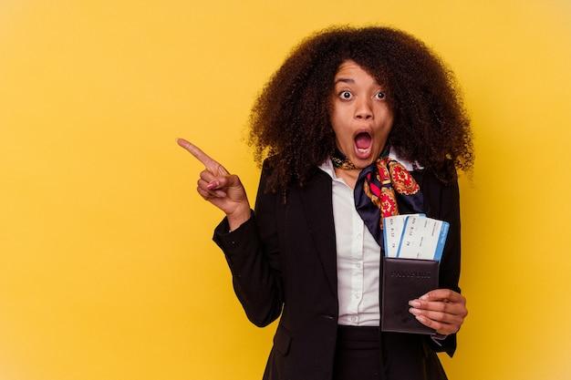 Młody afroamerykanin stewardesa trzyma bilety lotnicze na białym tle na żółtej ścianie, wskazując w bok