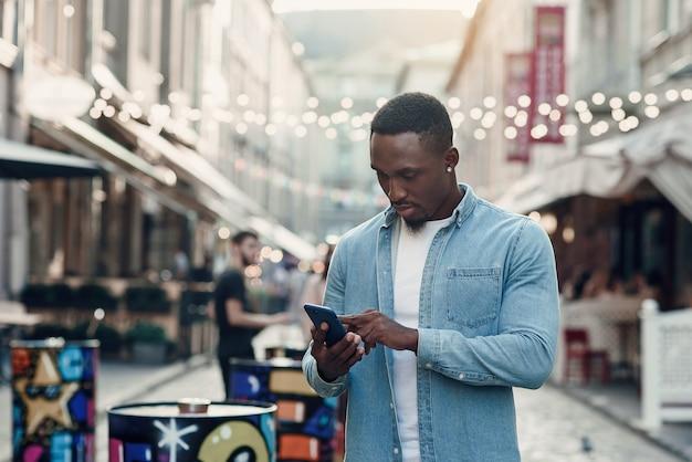 Młody afroamerykanin stojący na letniej ulicy i używający smartfona